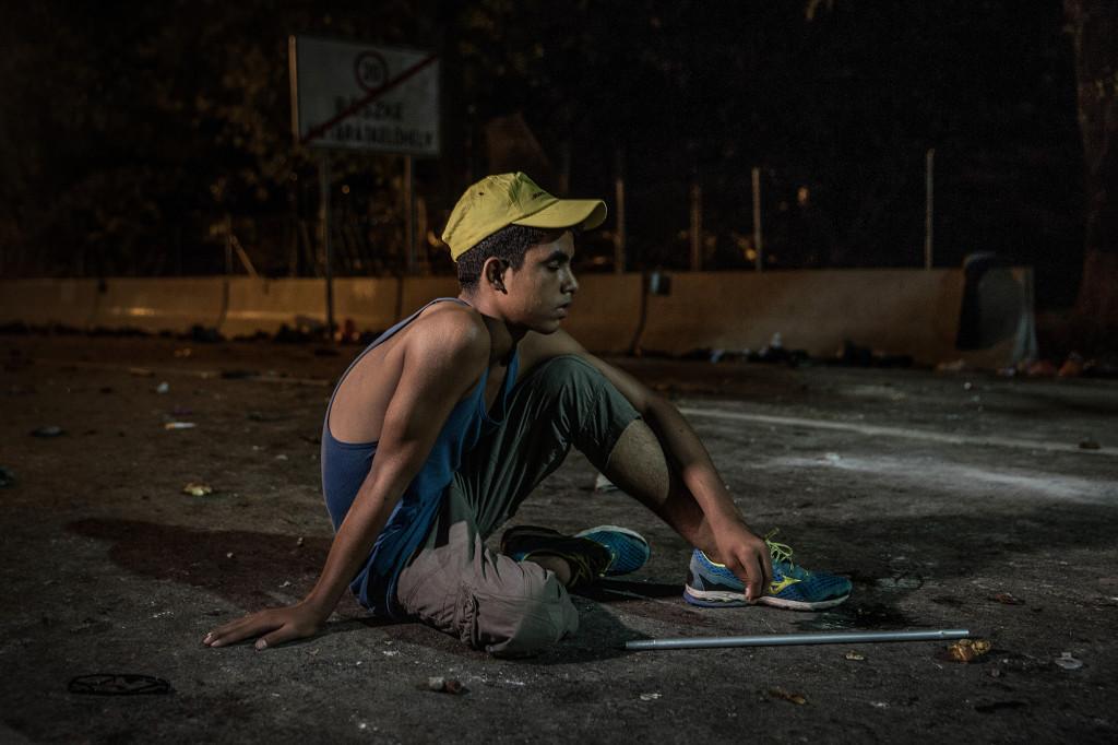 Abdullah, 14, sitter ensam på asfalten och stirrar mot stängslet. Hans pappa fördes bort av polisen vid den ungerska gränsen. Foto: MAGNUS WENNMAN