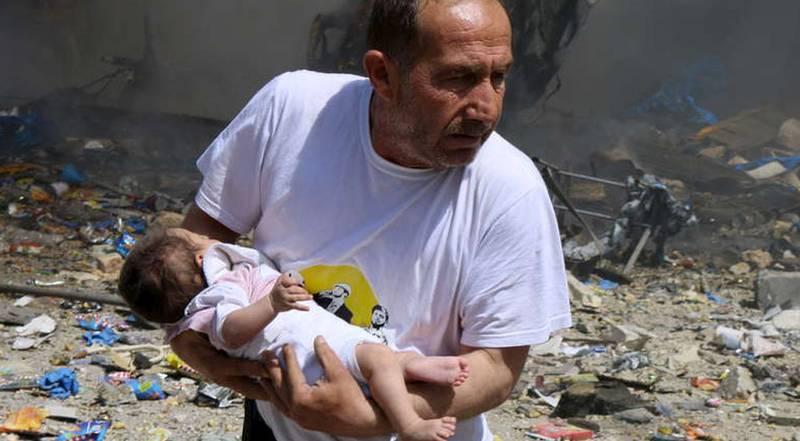 Mitt i kriget. En man med ett spädbarn efter ett bombangrepp av syriska regeringsstyrkor i staden Aleppo, juni 2015.